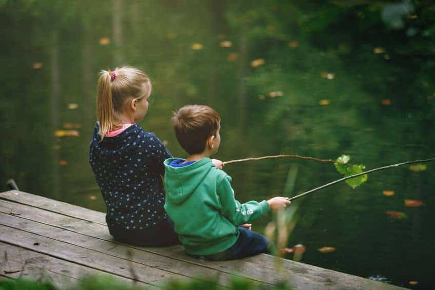 Small children sitting on a bench fishing on free dishing day.