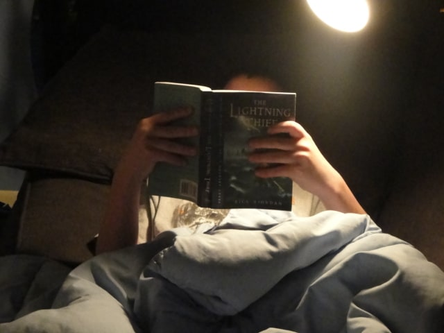 Young man reading Percy Jackson book.