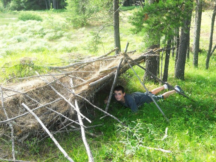Young man build a makeshift fort from twigs and shrubbery.