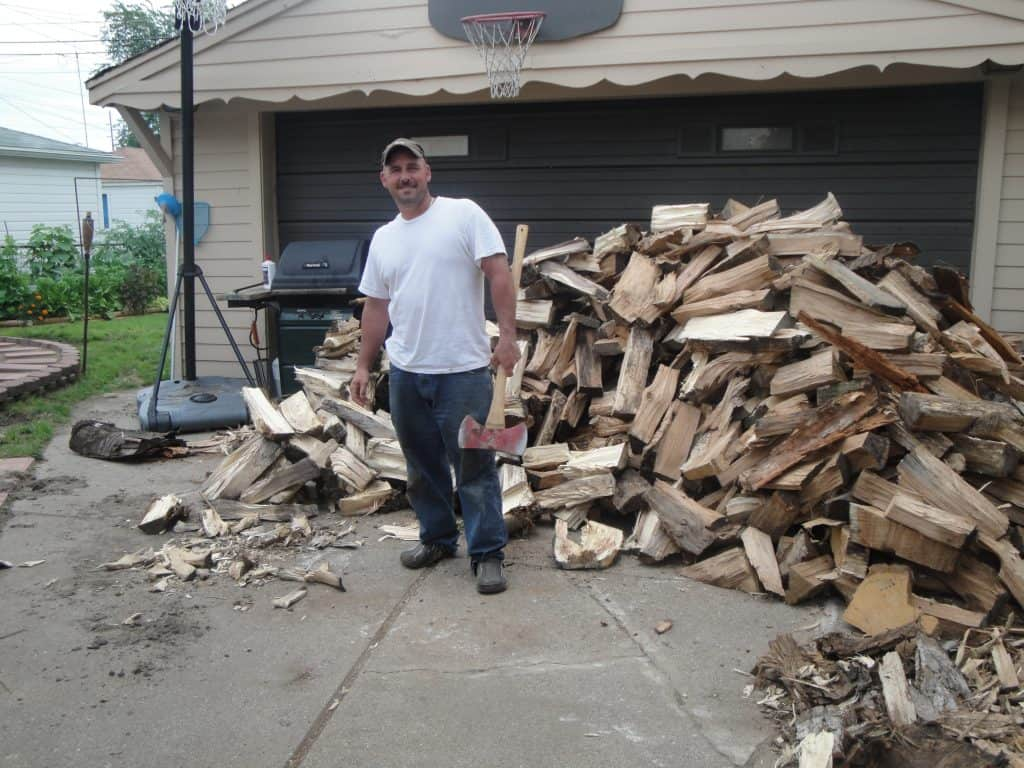 Man with a pile of cut wood.