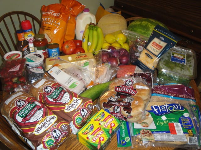 Table full of groceries from using coupons on grocery shopping trip.