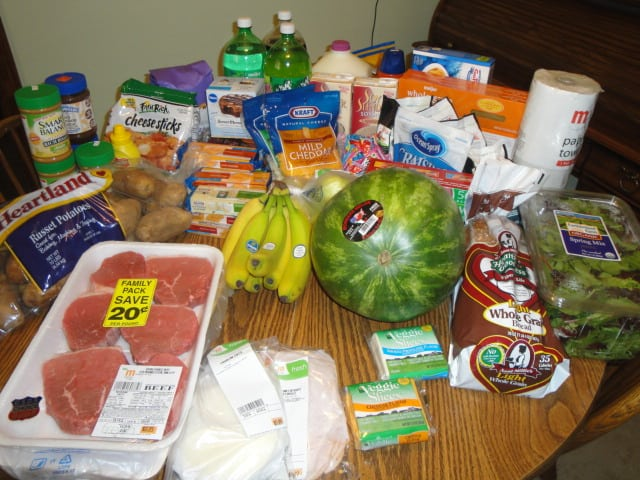Weekly shopping trip after couponing and price matching. A table full of fresh produce and meats.