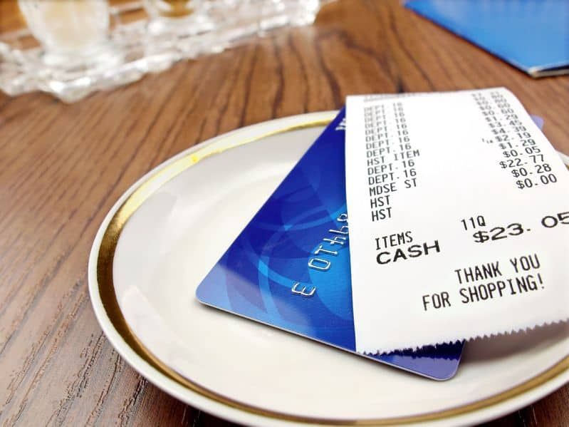 A dinner plate with credit card and bill on top.