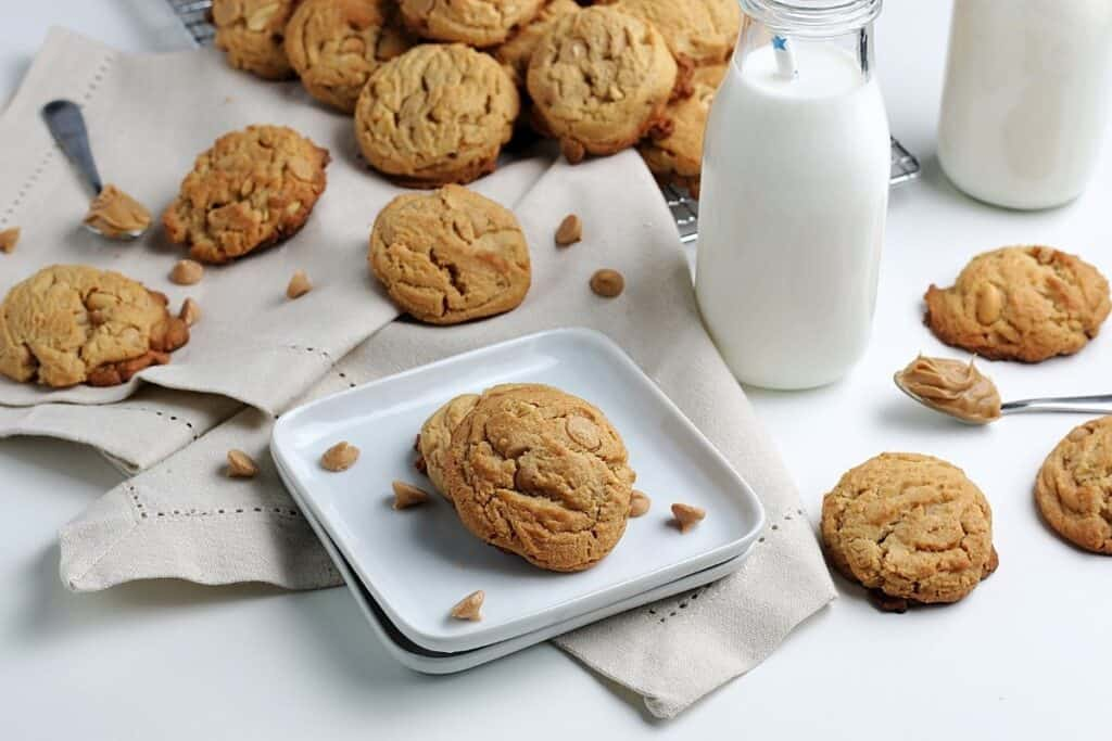 Peanut butter cookies scattered on plates and kitchen clothes with cups full of milk.