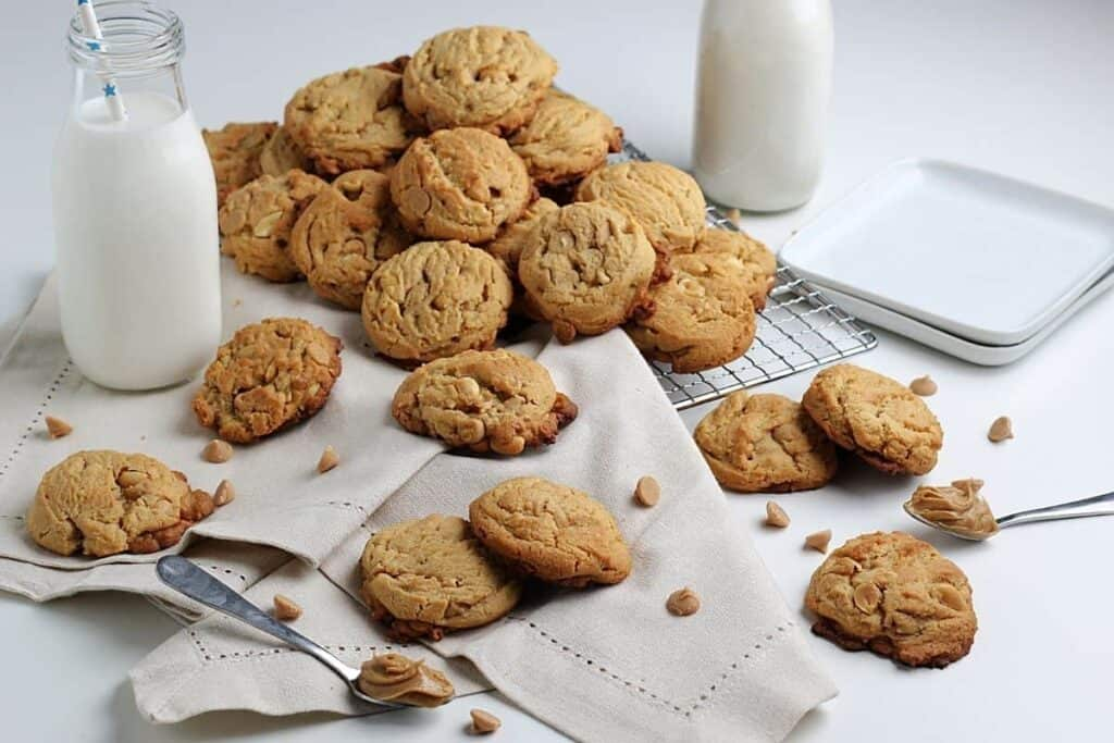 Peanut butter cookies surrounded by peanut butter chips and milk.