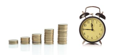 A stack of coins next to a clock.
