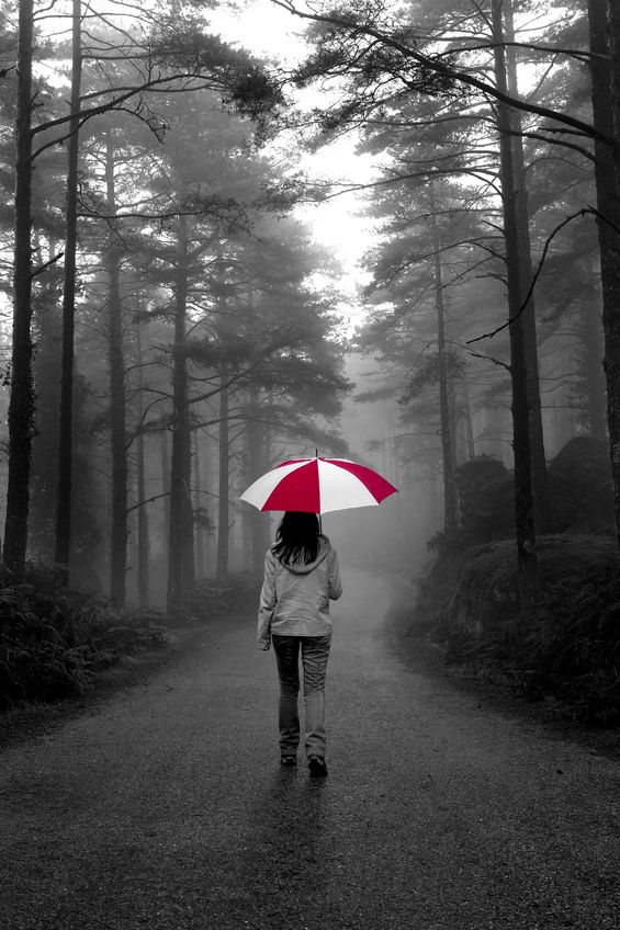 A woman walking in the rain holding an umbrella