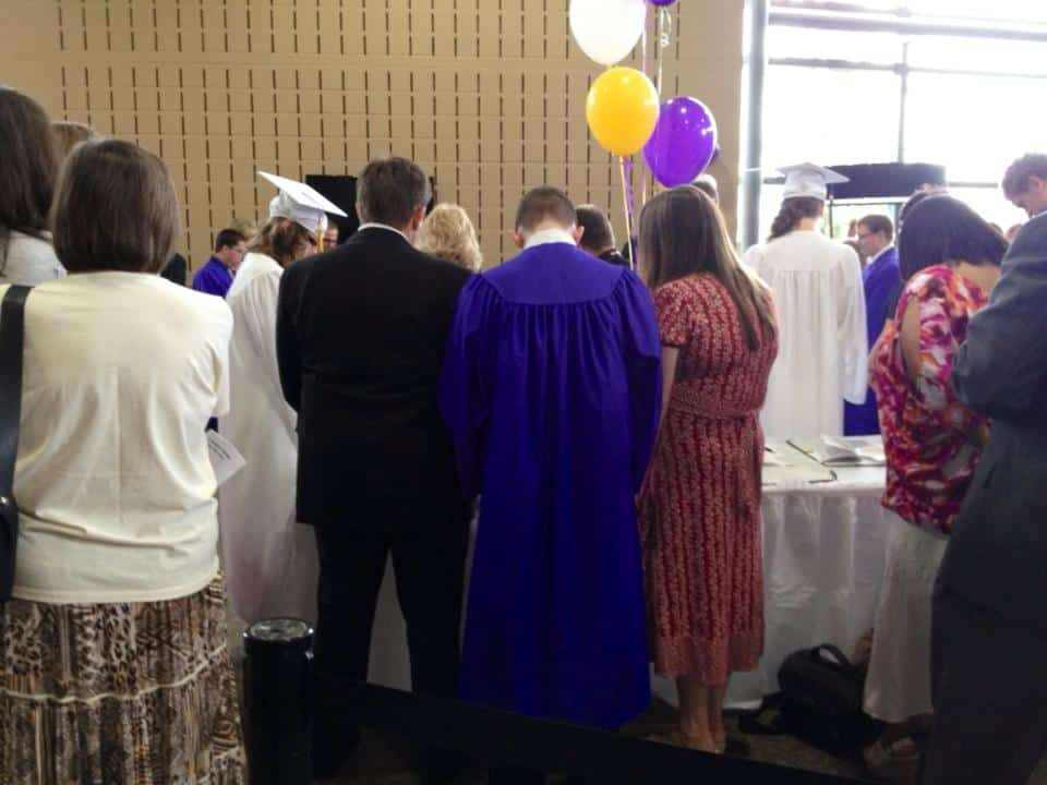 A group of people standing in front of a crowd of school graduates.