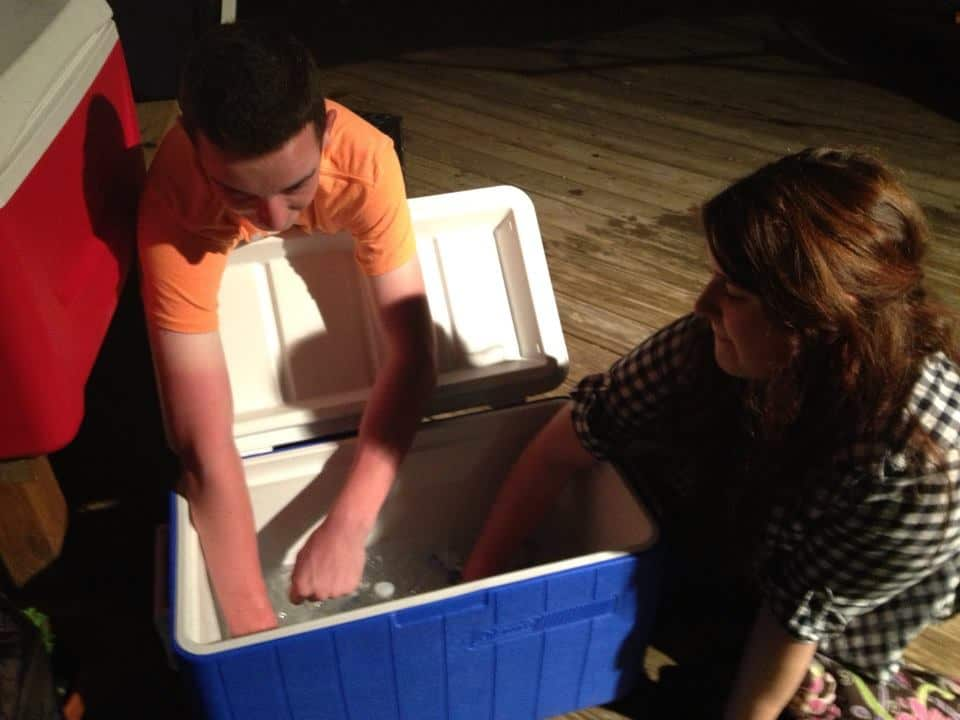 A group of people diving into a cooler and grabbing drinks.