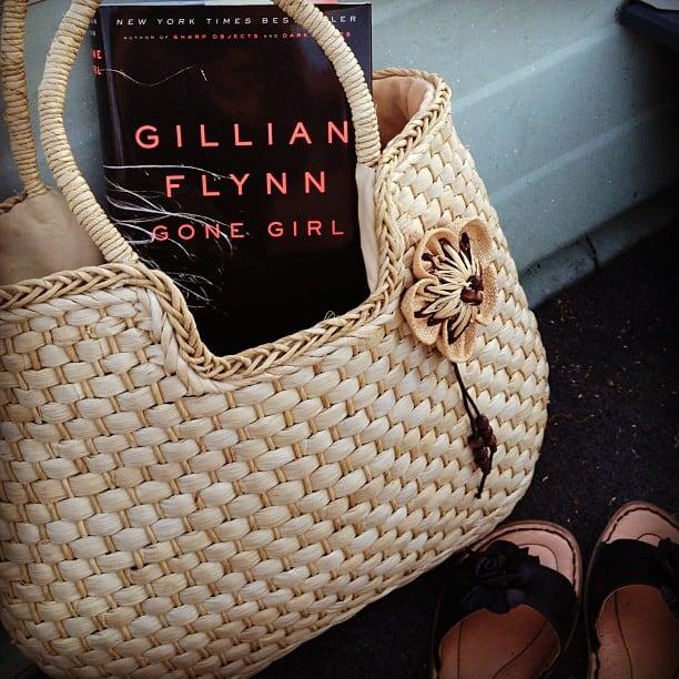 """Gillian Flynn\'s \""""Gone Girl\"""" book in a wicker purse."""