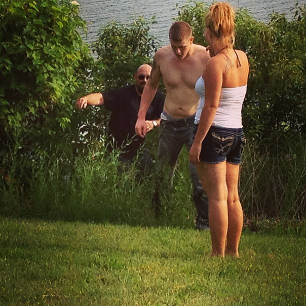 A couple of people that are standing in the grass
