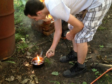 Young man burning an object in the woods.