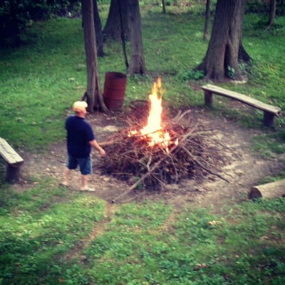 A man standing by a large pile of sticks and a bonfire.