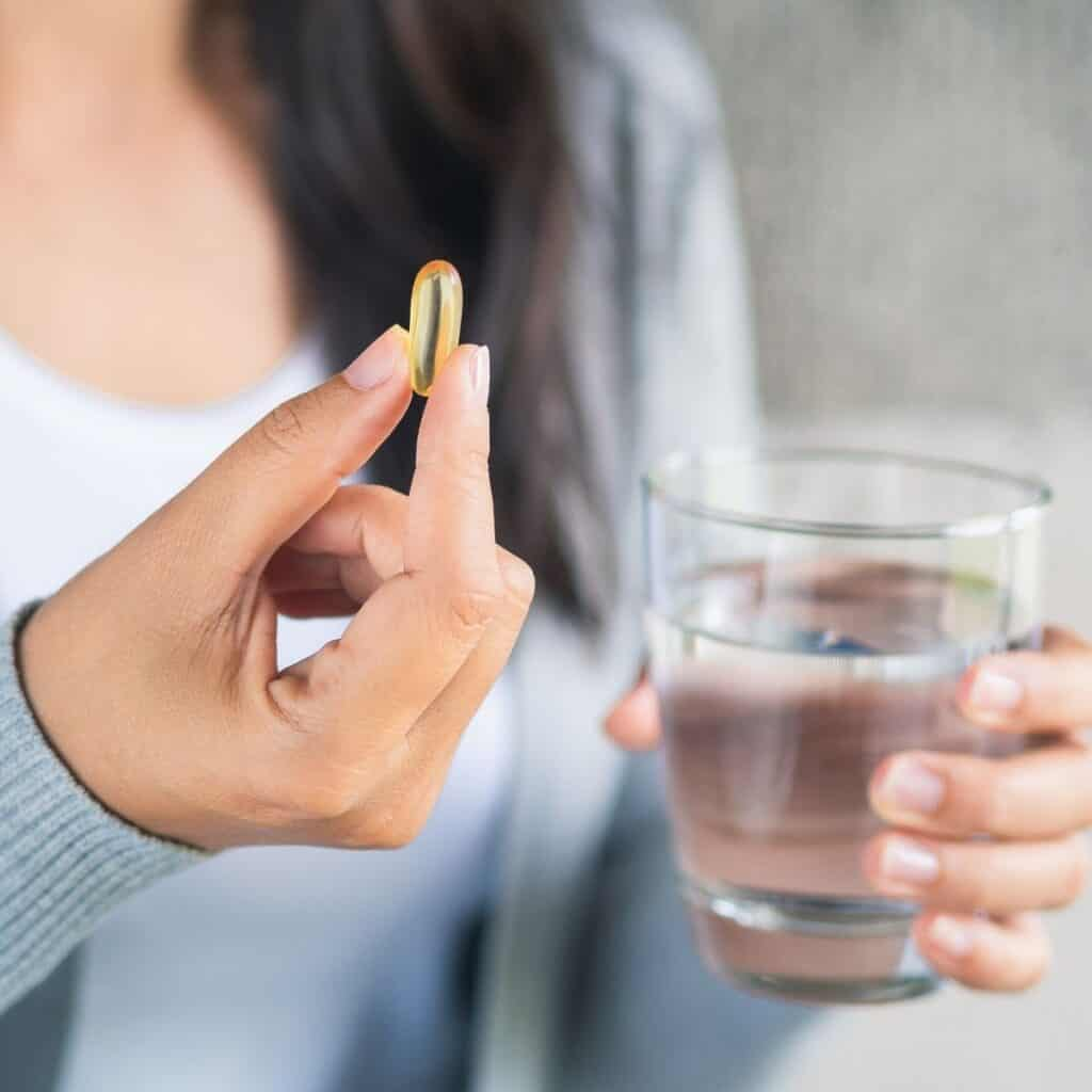A woman taking a pill with a drink of water.