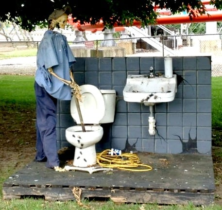 A Halloween decor of a skeleton using a plunger with the toilet in Cedar Point park.