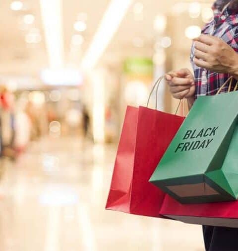Black Friday, Woman holding many shopping bags while walking in the mall.
