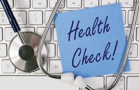 Health check sign on keyboard with stethoscope.