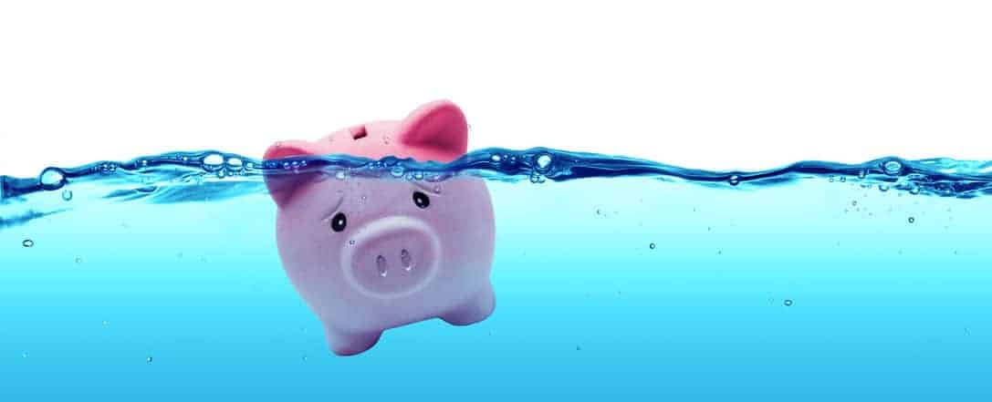 Sad piggy bank drowning in water due to having frugal burnout.