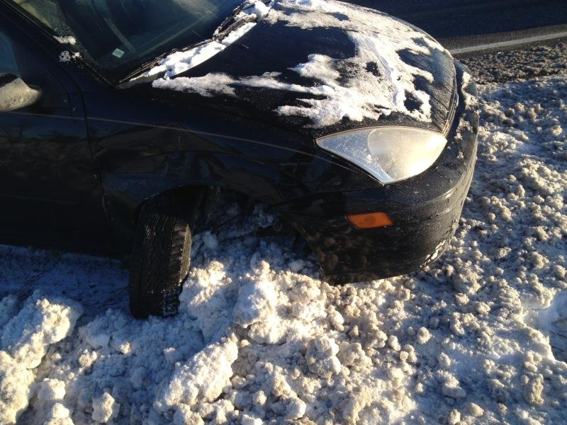How to not drive in the snow. A car with a broken axel and tire popped out on the side.