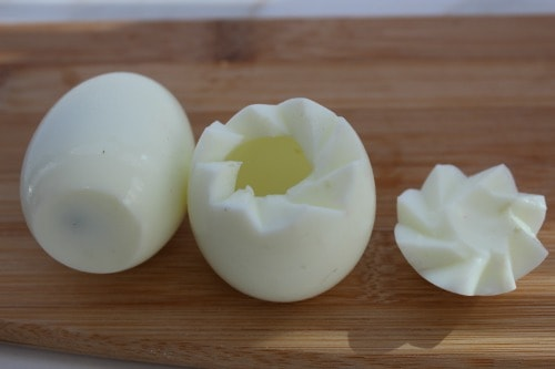 The top of a boiled egg cut out and the yolk removed.