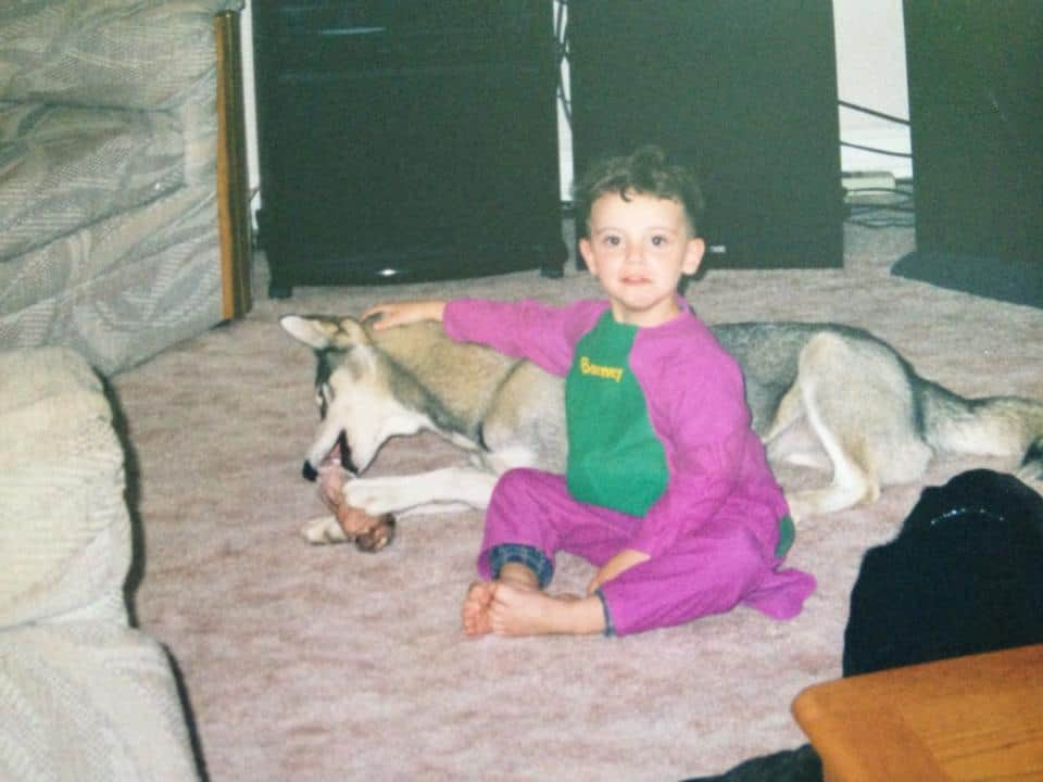 A small boy with a puppy dressed as Barney the dinosaur.