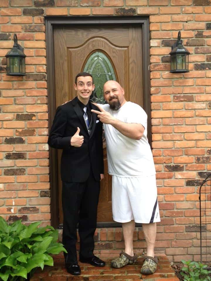 A father and son standing in front of their home door.