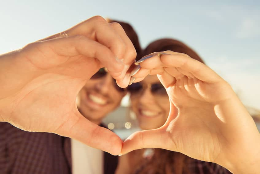 "A couple making a cute ""heart\"" with their hands together."