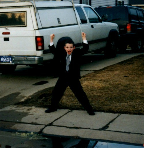 A little boy standing in front of a car