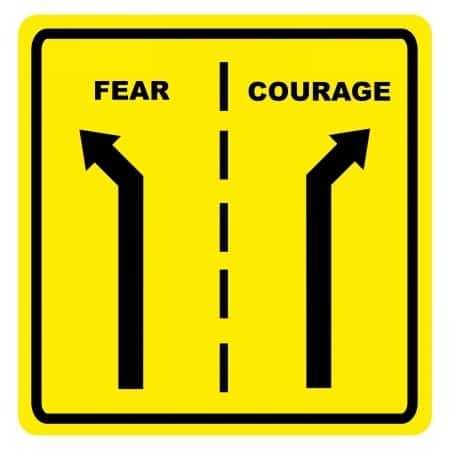A close up of a sign with two roads that divide between fear and courage.
