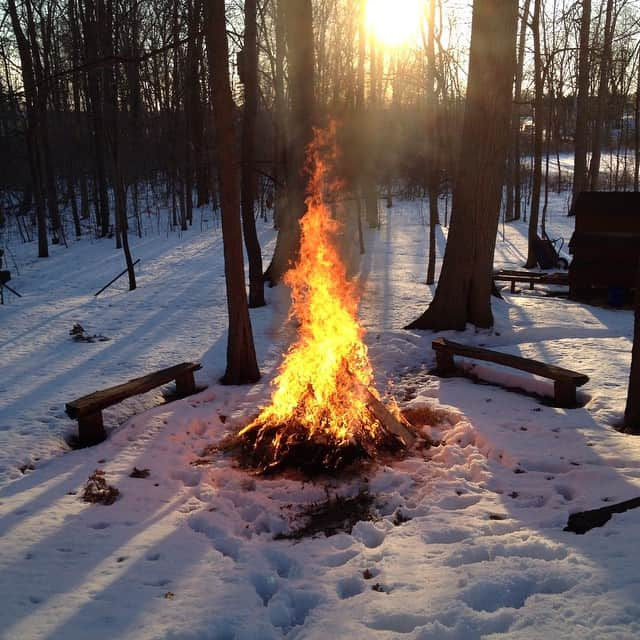 A bonfire in the middle of a field of snow.