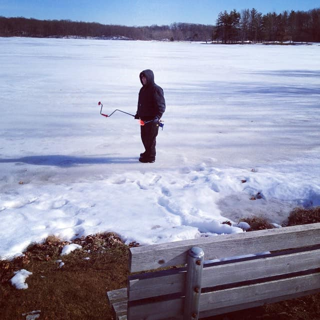 A man standing in the middle of a frozen lake going ice fishing.