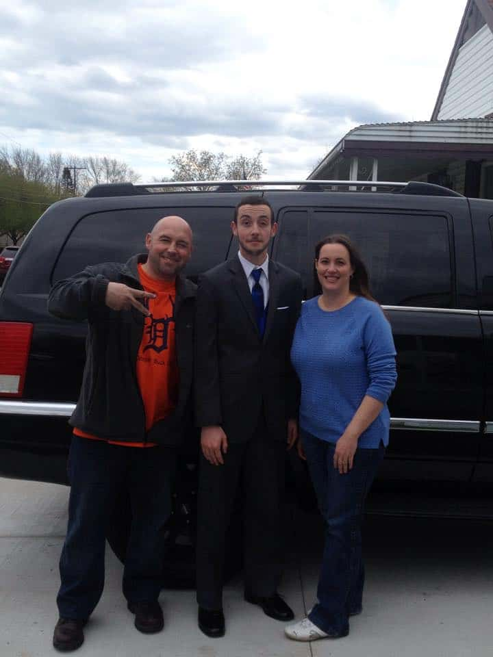 Parents with their young adult son who is dressed up in a suit and tie.