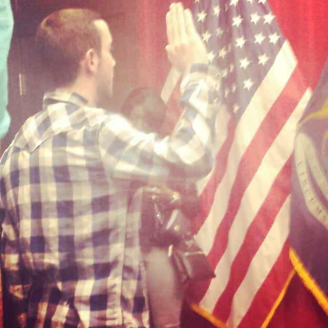 A young man raising his right hand to take an oath for the United States.