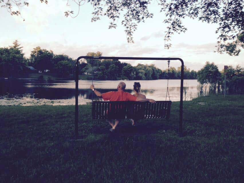 A man and woman sitting next to each other on a swinging bench by a body of water.