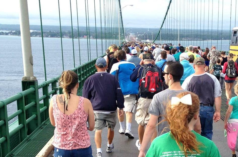 A group of people walking across the bridge over a large body of water.
