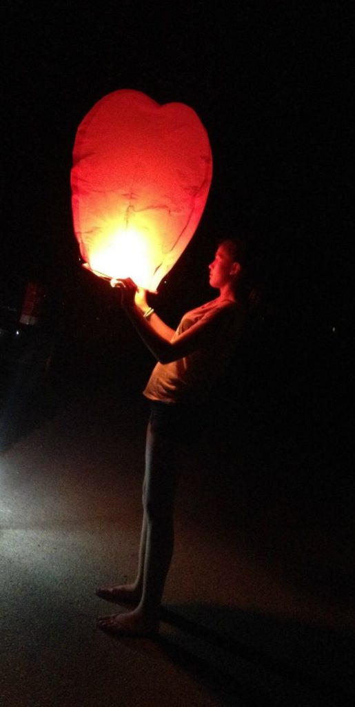 A person standing with a lit up lantern in the dark.