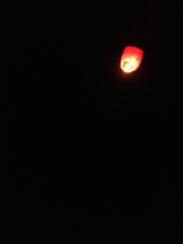 A close up of a lit lantern floating away in the sky.