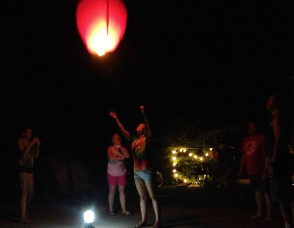 A group of people standing around a lighted lantern.