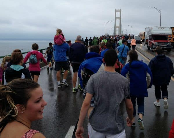 A large crowd of people taking a walk together across the bridge.
