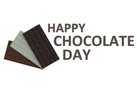"Several different types of chocolate bars with a sign that reads, ""Happy Chocolate Day.\"""