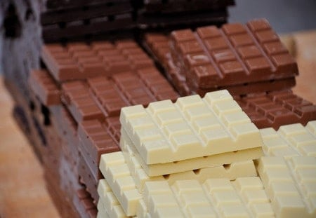 White chocolate bars and milk chocolate bars stacked on top of each other.