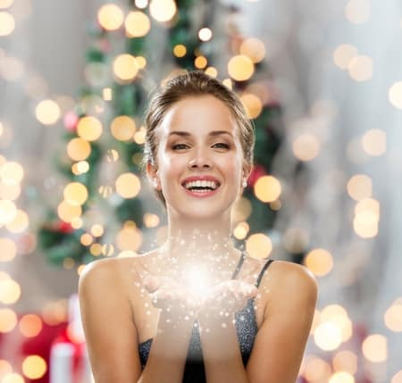 A woman smiling in front of a Christmas tree. How to Earn Extra Cash for the Holidays