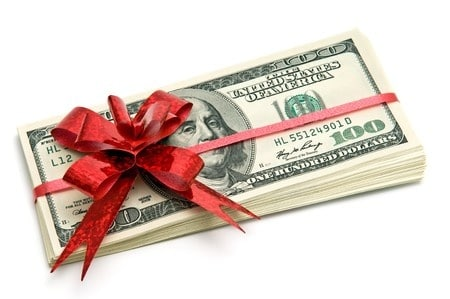 A stack of cash wrapped in a red Christmas bow. How to Earn Extra Cash for the Holidays