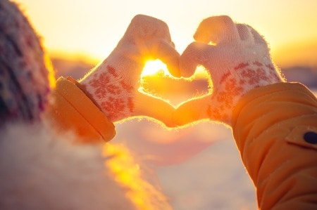 A woman holding her hands in a heart-shape against the snow and sunshine.