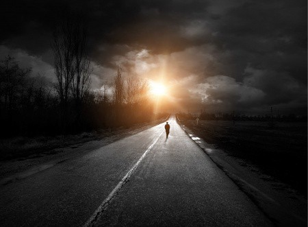 A lonely person walking down the road by them self.