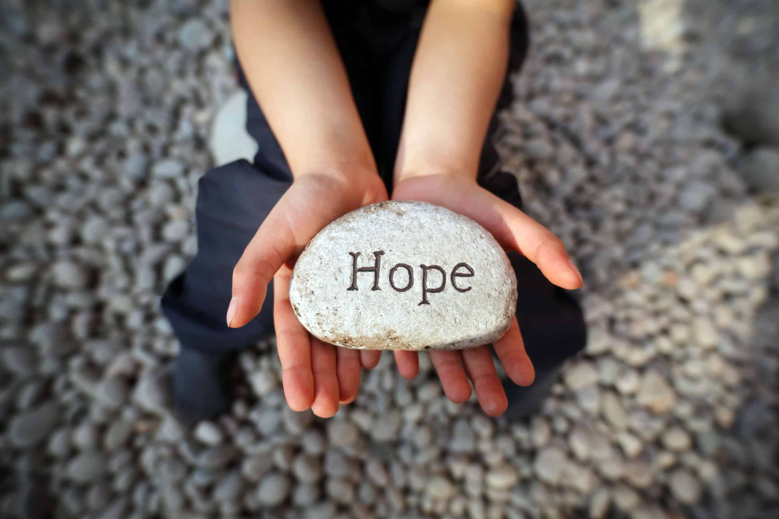 """A girl holding a rock with the word inscribed that reads, """"hope."""""""