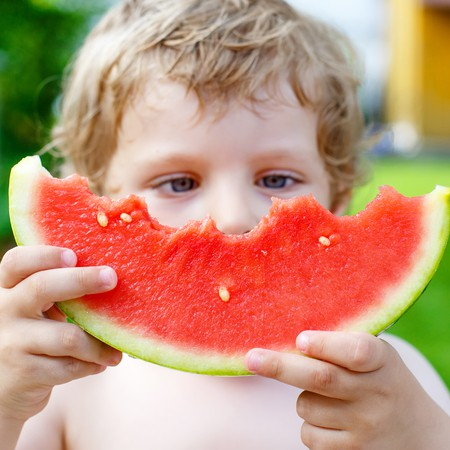 A close up of a kid holding a slice of partially eaten watermelon.