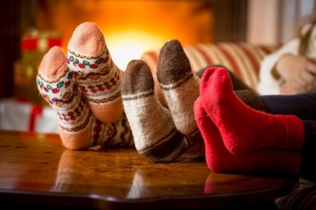 46546510 - closeup photo of family feet in wool socks at fireplace
