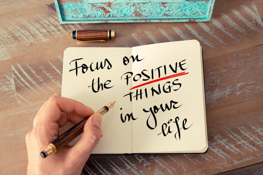 53741910 - retro effect and toned image of a woman hand writing a note with a fountain pen on a notebook. handwritten text focus on the positive things in your life as business concept image