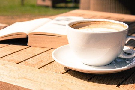 54109310 - coffee mug and a book on a wooden table